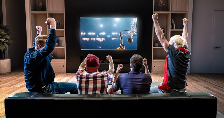 Un grupo de amigos que están viendo los deportes